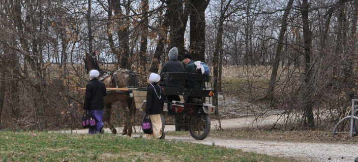 Children head home from school, some on foot, some riding a horse-drawn cart.