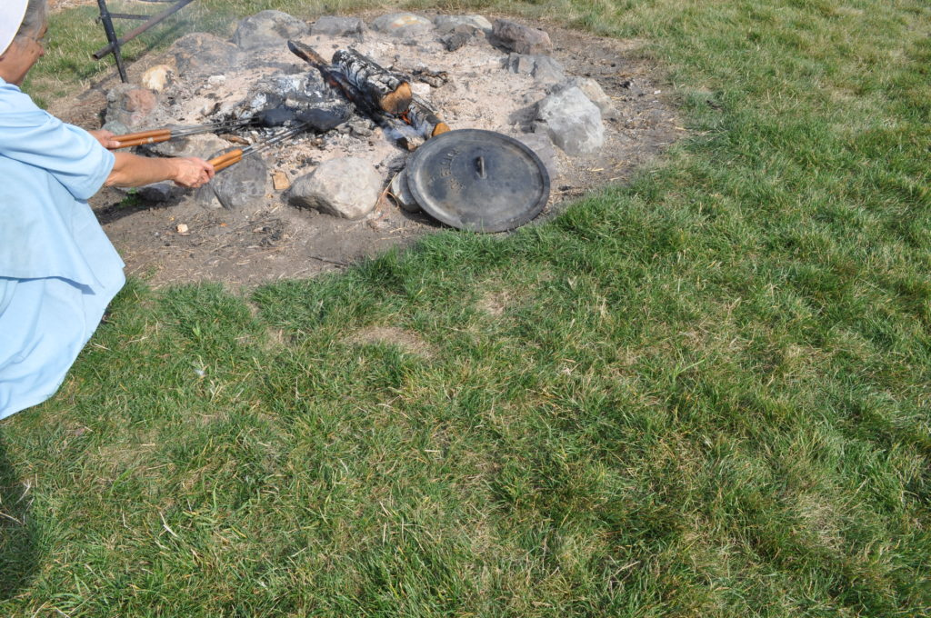 An Amish woman in St. Ignatius, Montana holds a mountain pie iron over an open fire.