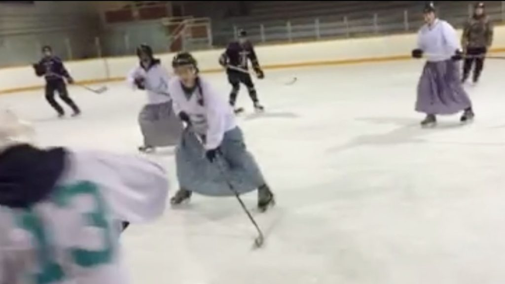 Hutterite girls in a blur of bonnets and dresses and sticks and pucks remained undefeated in their match against the ladies in the nearby town.  The charity match raised $400 this year. (CBC photo)