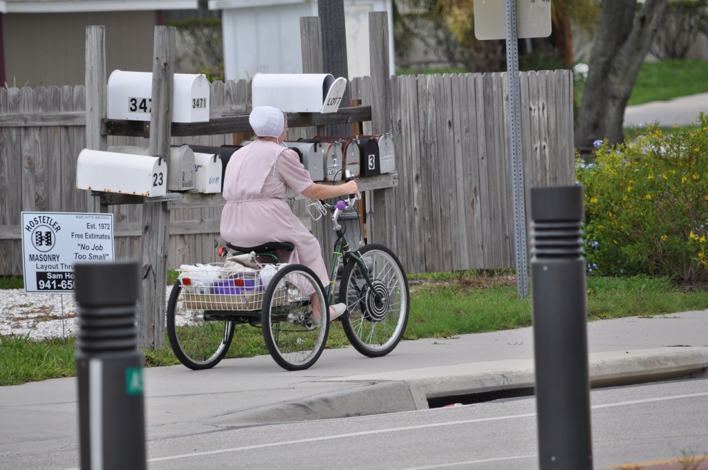 An Amish woman pedals down a Pinecraft street. Buggies won't be found here, just bikes.