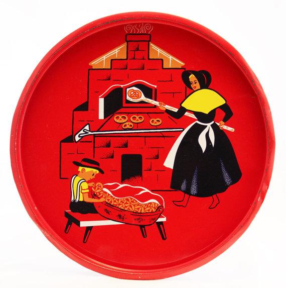 A serving tray depicting an Amish woman making pretzels....