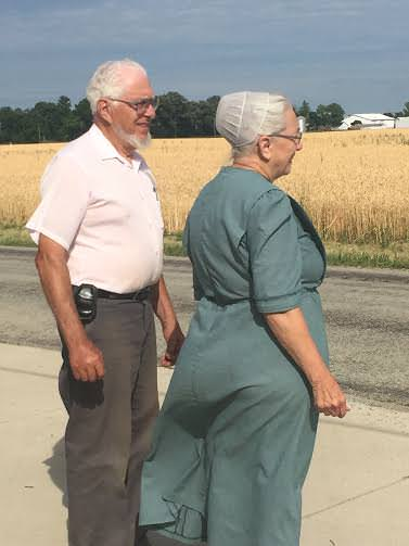 Enos and Mary Stutzman gaze towards a golden wheat field. Stutzman says that the Amish are more accommodating today to varying views and that if some of their life events had occurred today, they would have remained Amish.