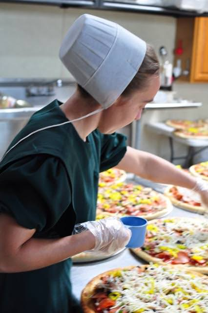 Another worker adds toppings...
