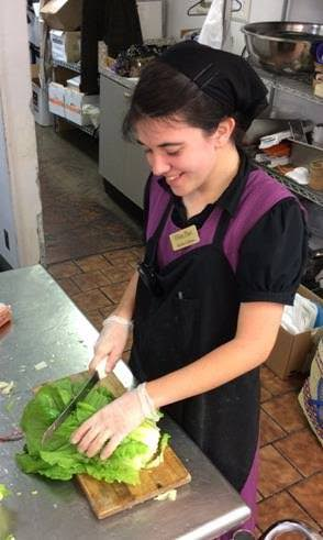 One of the Home Place workers prepares a fresh lettuce salad