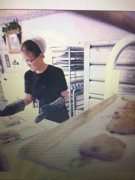Lydia Helmuth tends to fresh loaves of bread at Backermans