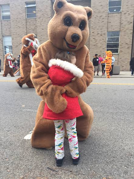 My 3-year-old daughter is a sociable little one.  At my town's annual Christmas parade, she gladly accepted a hug from one of the many costumed characters.  As an aside, in the background, is the stately old Middletown Journal building where I worked from 1989 - 2000.  Lots of memories there.  The old brick building would literally tremble when the printing presses roared to life each afternoon.   The building has sat vacant now for almost a decade perhaps awaiting a second life as apartments.  The newspaper has since been folded into one county wide paper.